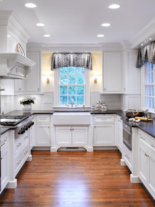 This Grey and white country farmhouse kitchen has both a warm rustic feel to it and modern lines and appearance.  The dark counter tops accent the white cabinets and brick backsplash perfectly. The wood floors tie it all together. Just beautiful!