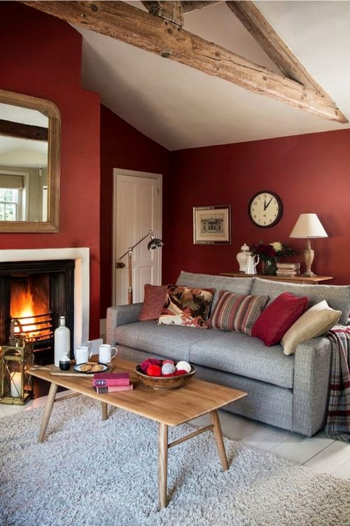 Cozy comfy small living room ideas in warm colors - love this red / burgandy living room wall paint color with the gray couch - looks great!